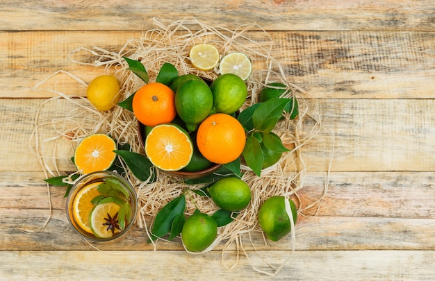 Top view tangerines in pot with herbal tea on wooden board