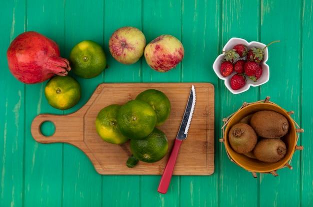 Vista dall'alto mandarini con un coltello su un tagliere con mele melograno kiwi e fragole