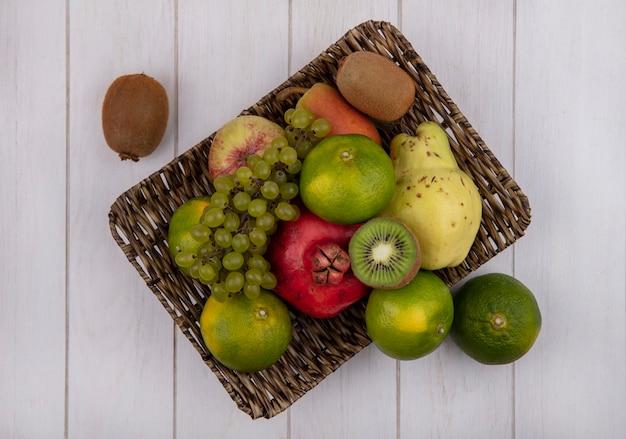 Вид сверху мандарины с гранатом, грушей, яблоком, виноградом и киви в корзине
