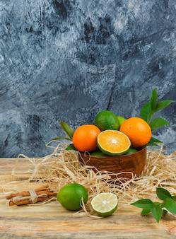 Vista dall'alto di mandarini in ciotola di legno con cannella, limette e foglie su tavola di legno e superficie in marmo blu