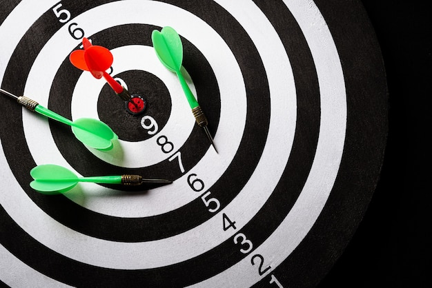 Top view of a target dartboard with arrows on dark wall