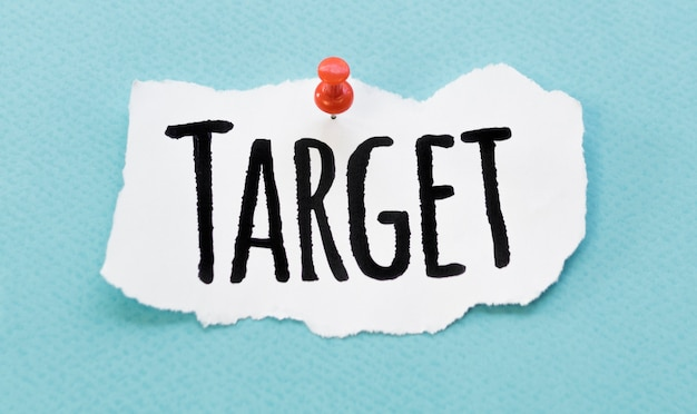 Top view of target written on piece of paper with pin