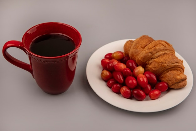 Top view of tart sweet cornelian cherries with croissant on a white plate with a cup of coffee on a grey wall