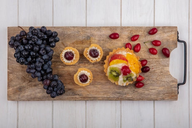 Top view tartlets with black grapes and dogwood on a cutting board
