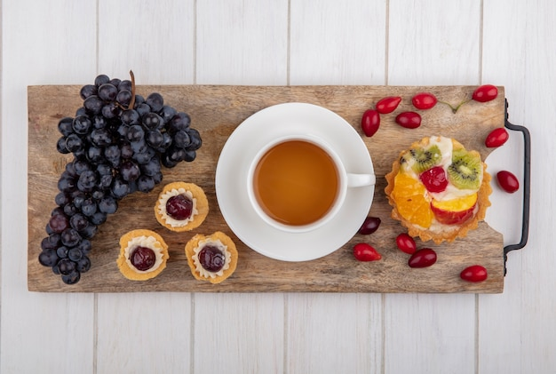 Top view tartlets with a cup of tea  black grapes and dogwood on a cutting board