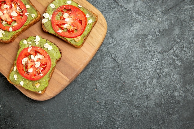Top view tasty avocado sandwiches with sliced red tomatoes on the grey background burger sandwich bread bun snack