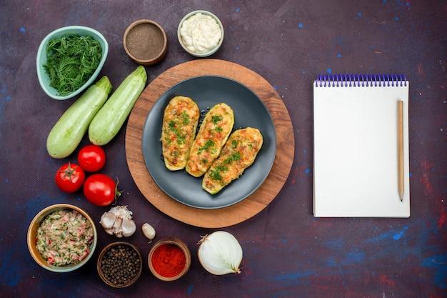 Vista dall'alto di gustose zucche al forno con verdure insieme a condimenti di verdure fresche sulla superficie scura