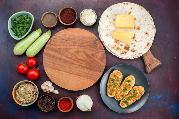 Vista dall'alto di gustose zucche al forno con verdure insieme a condimenti, carne, pane pita e verdure fresche sulla superficie scura