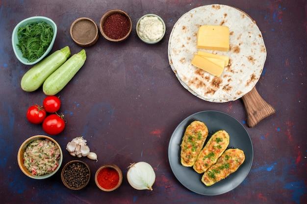Vista dall'alto di gustose zucche al forno con verdure insieme a condimenti di carne pita e verdure fresche sulla superficie scura