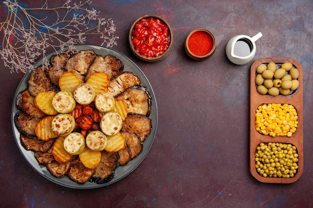 Top view tasty baked vegetables potatoes and eggplants on a dark background meal oven cooking bake vegetables