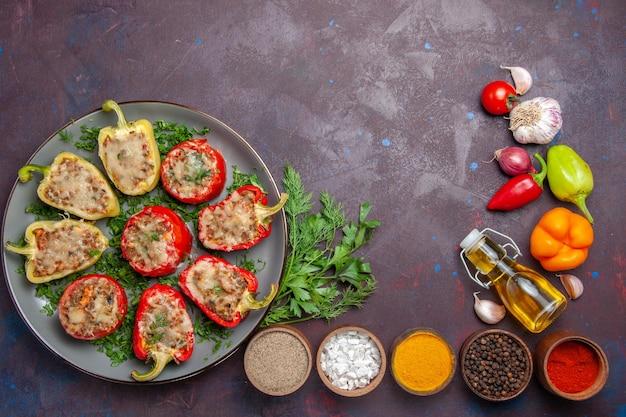 Vista dall'alto gustosi peperoni deliziosi pasto cotto con carne e verdure su piatto di superficie scura cena cibo
