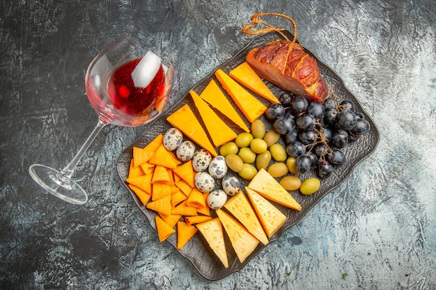 Top view of tasty best snack on a brown tray and fallen wine glass on ice background