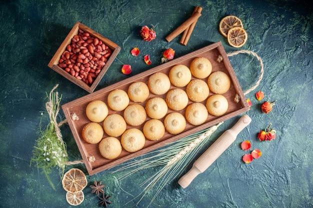 Top view tasty biscuits inside wooden box on dark background sugar cookie biscuit pie color sweet nut tea cakes
