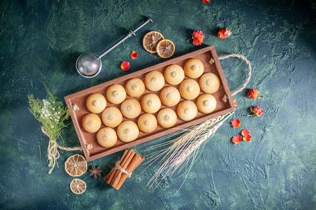 Top view tasty biscuits inside wooden box on dark blue background sugar cookie biscuit pie color sweet nut tea cake
