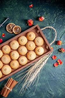Top view tasty biscuits inside wooden box on dark blue background sugar cookie biscuit pies color sweet nut tea cake
