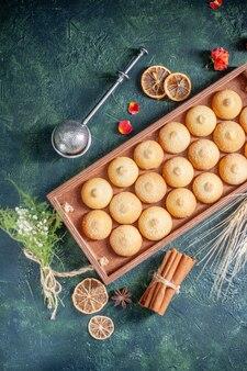 Вид сверху вкусное печенье внутри деревянной коробки на темно-синем фоне сахарное печенье бисквитный пирог цвет сладкий ореховый чайный торт