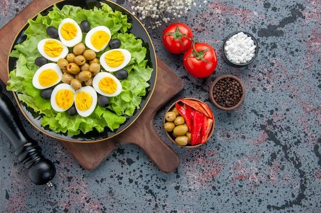 Вид сверху вкусные вареные яйца с зеленым салатом, оливками и помидорами на светлом фоне
