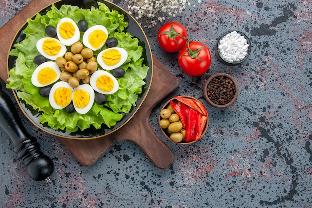 Top view tasty boiled eggs with green salad olives and tomatoes on light background