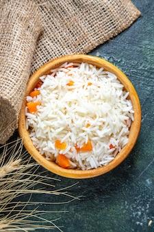 어두운 책상에 작은 접시 안에 상위 뷰 맛있는 삶은 쌀