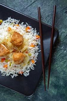 어두운 책상에 접시 안에 콩과 고기와 상위 뷰 맛있는 삶은 쌀