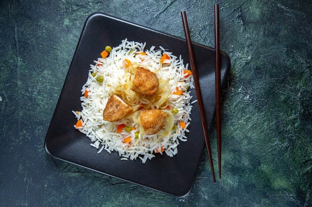 Vista dall'alto gustoso riso bollito con fagioli e carne all'interno del piatto sulla scrivania scura