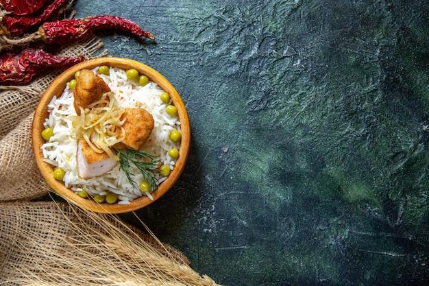 어두운 책상에 녹색 콩과 고기와 함께 맛있는 삶은 쌀을보기