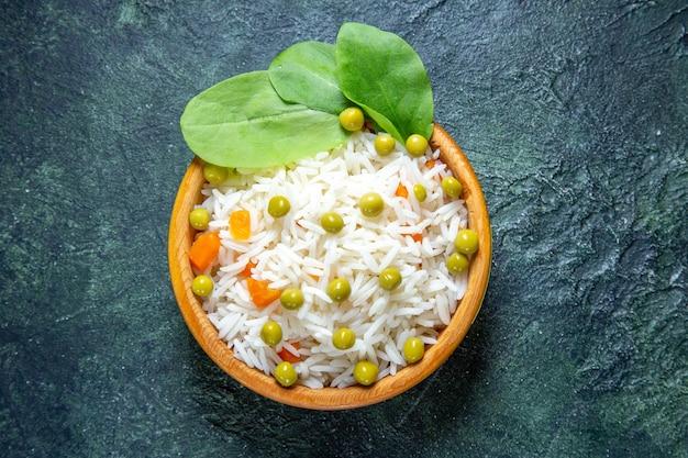 어두운 책상에 작은 접시 안에 녹색 콩 상위 뷰 맛있는 삶은 쌀
