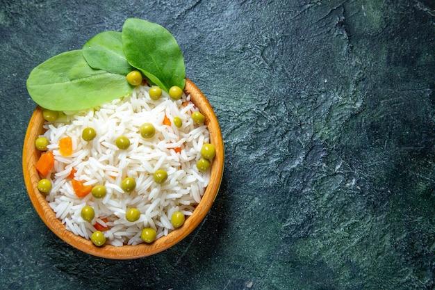 Вид сверху вкусный вареный рис с зеленой фасолью внутри маленькой тарелки на темном столе