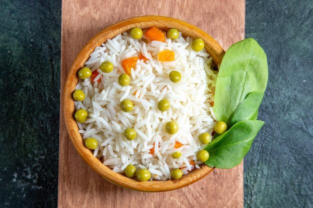 어두운 책상에 접시 안에 녹색 콩 상위 뷰 맛있는 삶은 쌀