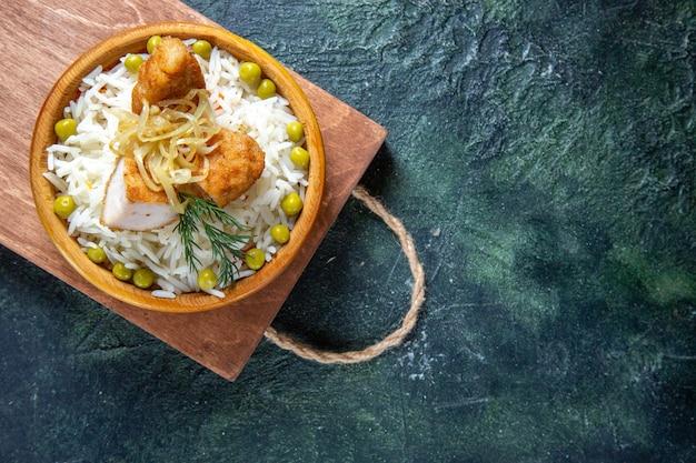 Vista dall'alto gustoso riso bollito con fagiolini e carne sulla scrivania scura