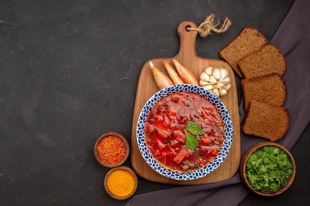 Top view tasty borsch ukranian beet soup with dark bread loafs on the dark space