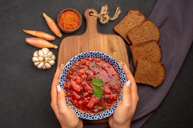 Вид сверху вкусный борщ украинский свекольный суп с темными буханками хлеба на темном пространстве