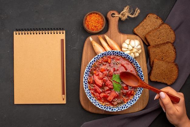暗い空間に暗いパンのパンとおいしいボルシチウクライナのビートスープの上面図