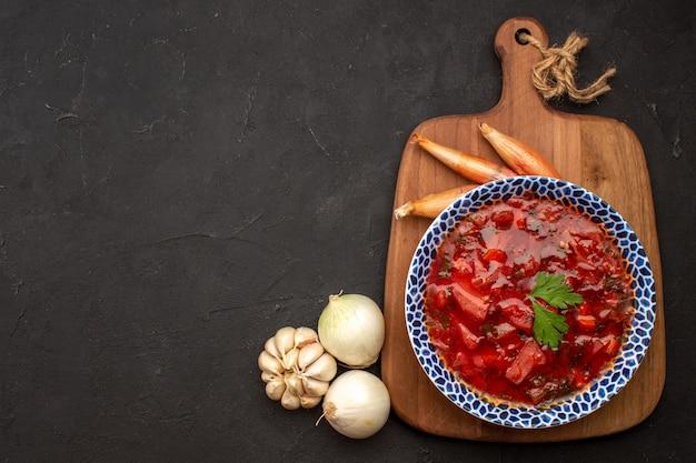 Vista dall'alto gustosa zuppa di barbabietola borsch ucraina con aglio su spazio scuro