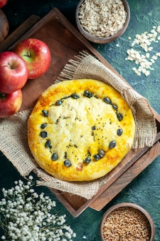 Vista dall'alto gustose mele da pane su tavola di legno rettangolare avena e chicchi di grano in ciotole piccoli fiori bianchi sul tavolo