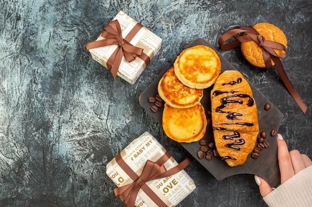 Top view of tasty breakfast with pancakes croisasant stacked cookies beautiful gift boxes on dark surface