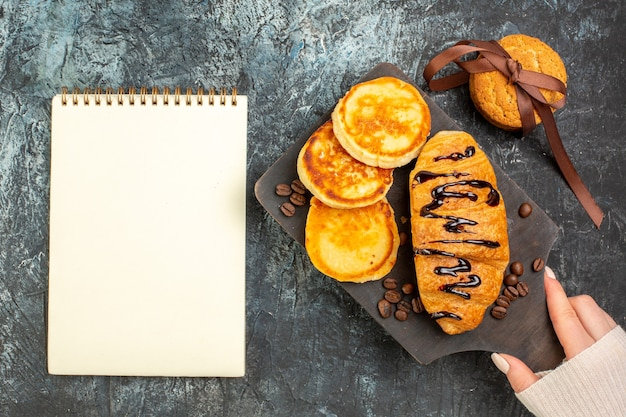 Top view of tasty breakfast with pancakes croisasant stacked cookies and notebook on dark surface