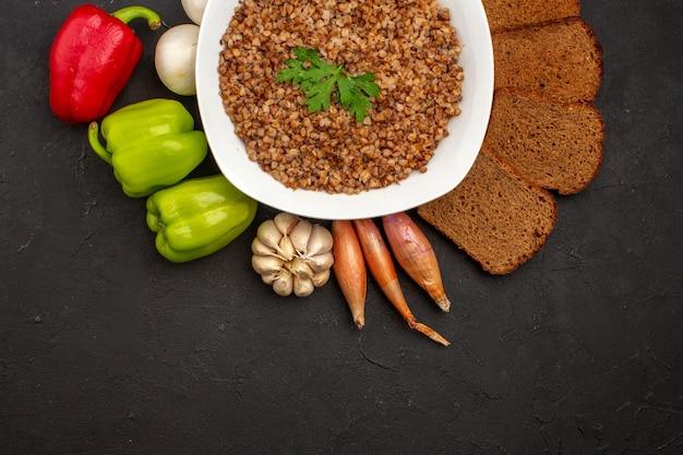 어두운 공간에 야채와 어두운 빵 덩어리가있는 상위 뷰 맛있는 메밀 식사