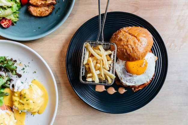Top view of tasty burger with fried egg served with fries in black plate on wooden table.