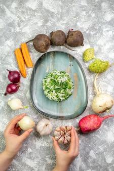 白いテーブルの上に新鮮な野菜とトップビューのおいしいキャベツのサラダ