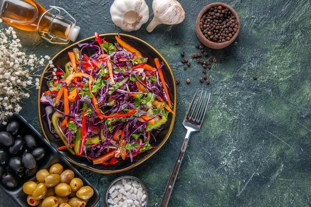 Vista dall'alto gustosa insalata di cavolo con peperoni all'interno della piastra su sfondo scuro pasto salute spuntino dieta pranzo vacanza cibo