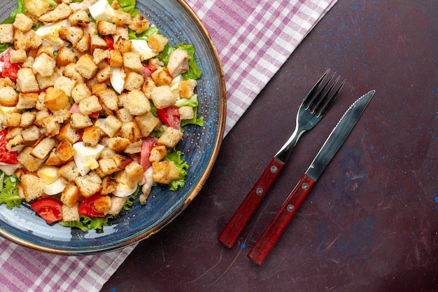 Vista dall'alto gustosa insalata caesar con posate sulla scrivania scura