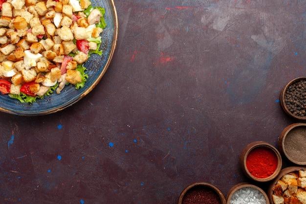 Vista dall'alto gustosa insalata caesar con diversi condimenti sulla scrivania buia