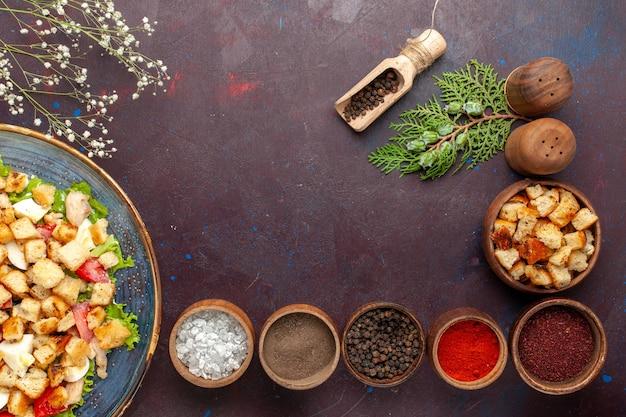 Vista dall'alto gustosa insalata caesar con diversi condimenti sulla superficie scura