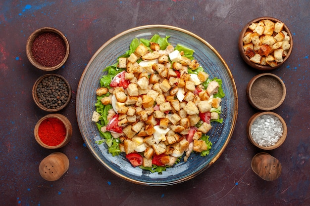 Top view tasty caesar salad with different seasonings on the dark surface