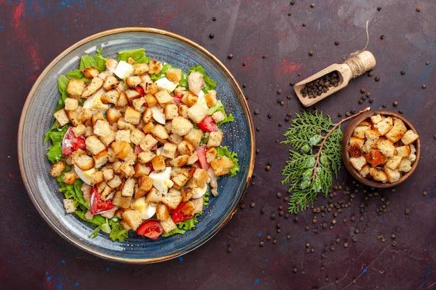 Vista dall'alto gustosa insalata caesar con piccole fette biscottate sulla scrivania scura