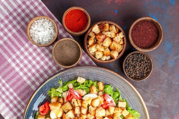 Vista dall'alto gustosa insalata caesar con piccole fette biscottate e condimenti sulla scrivania buia