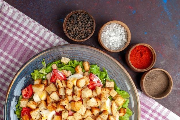 Vista dall'alto gustosa insalata caesar con condimenti sulla scrivania scura