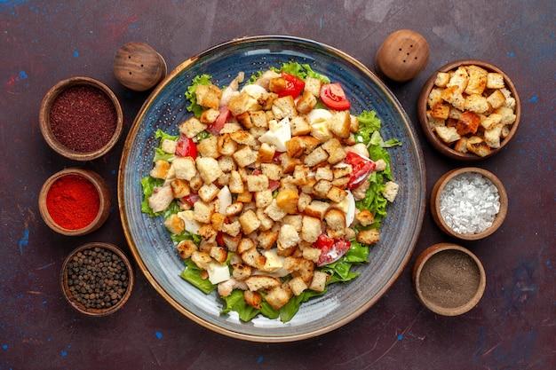 Top view tasty caesar salad with seasonings on dark surface
