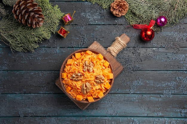 Top view tasty carrot salad with walnuts on dark-blue background health salad color diet food nut